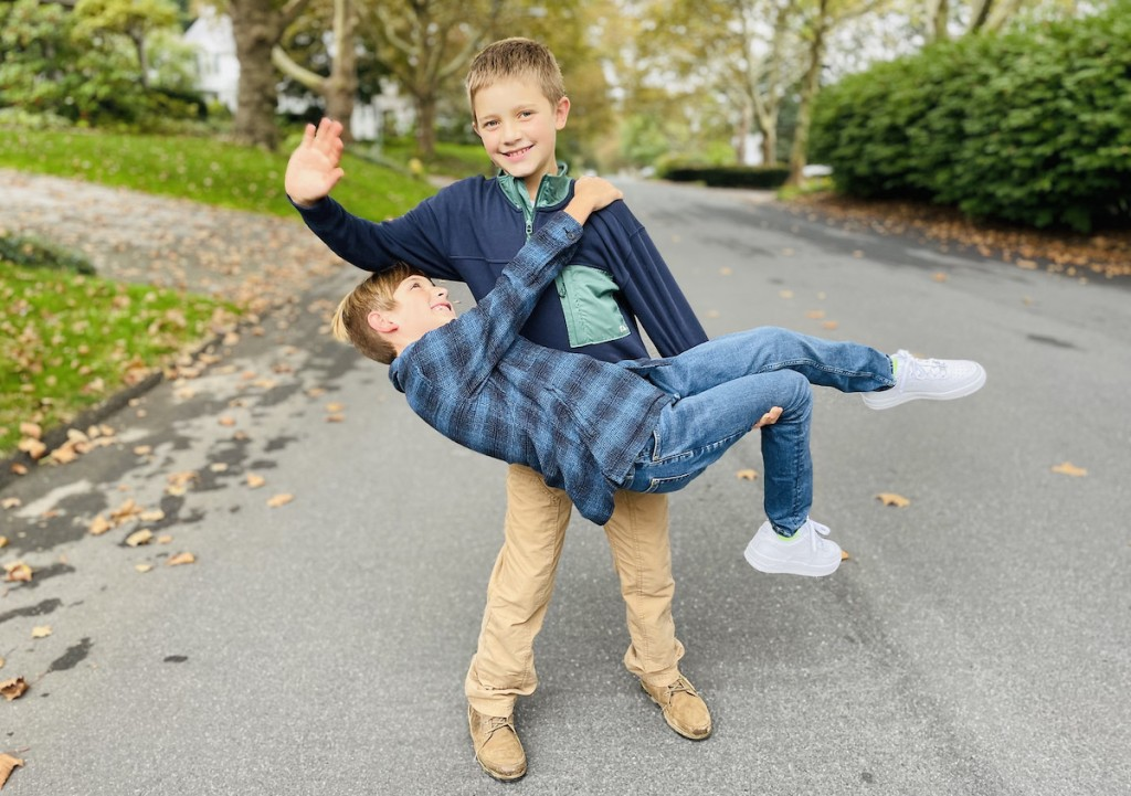 two boys standing in street goofing off