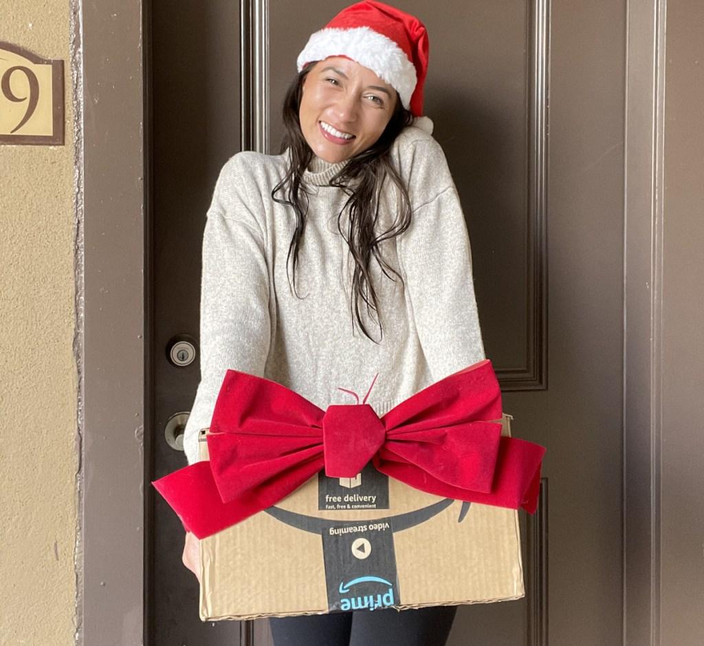 woman in santa hat holding amazon box near door