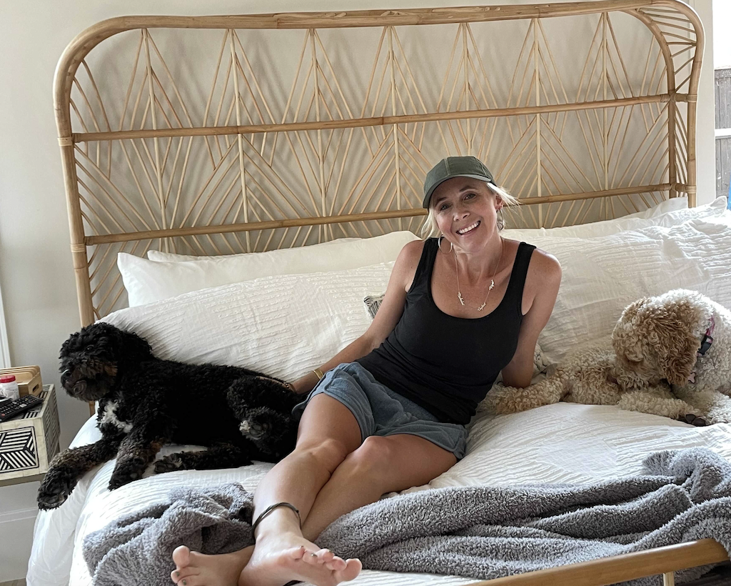 woman on bed with two dogs