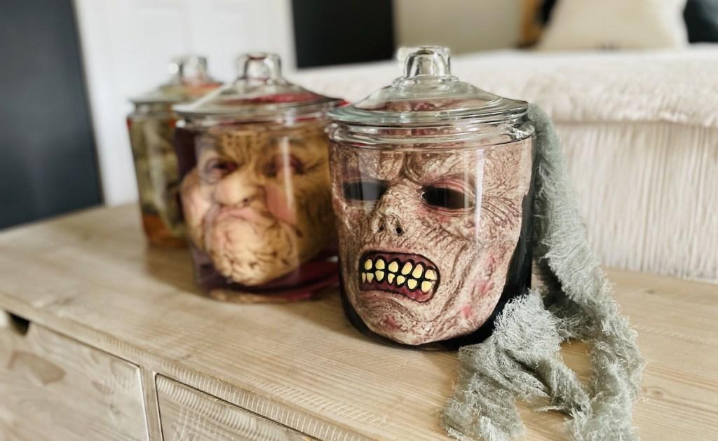 creepy halloween face masks in jars on wood storage bench